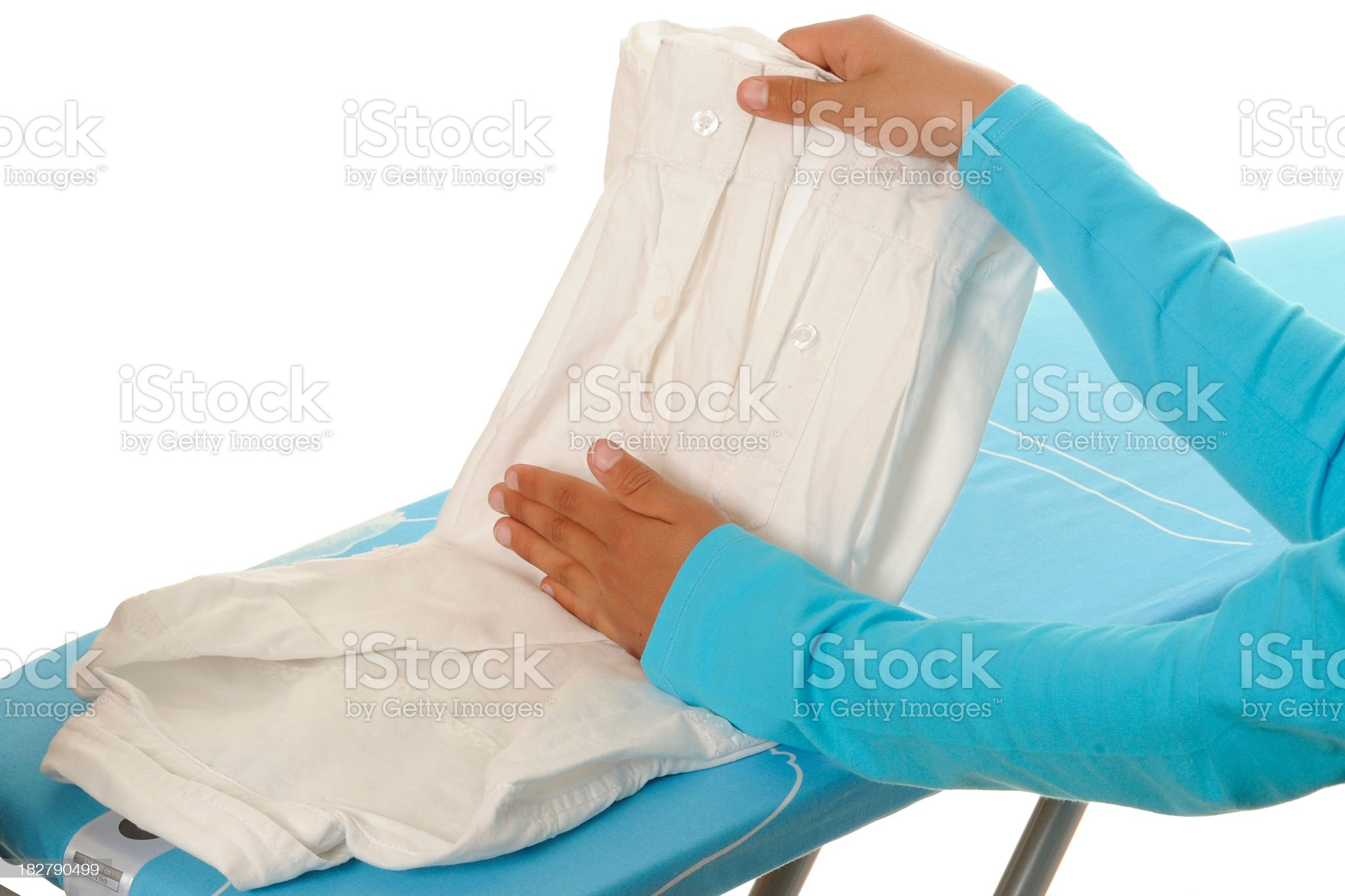 Folding a blouse on an ironing board royalty-free stock photo