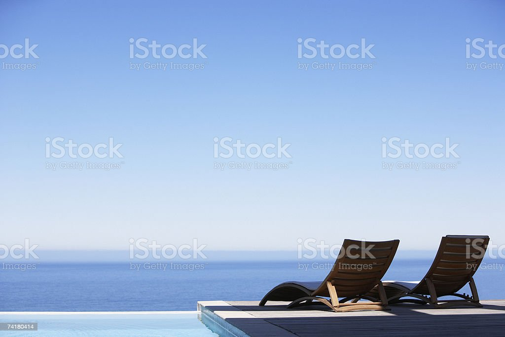 Folding chairs on infinity pool deck stock photo