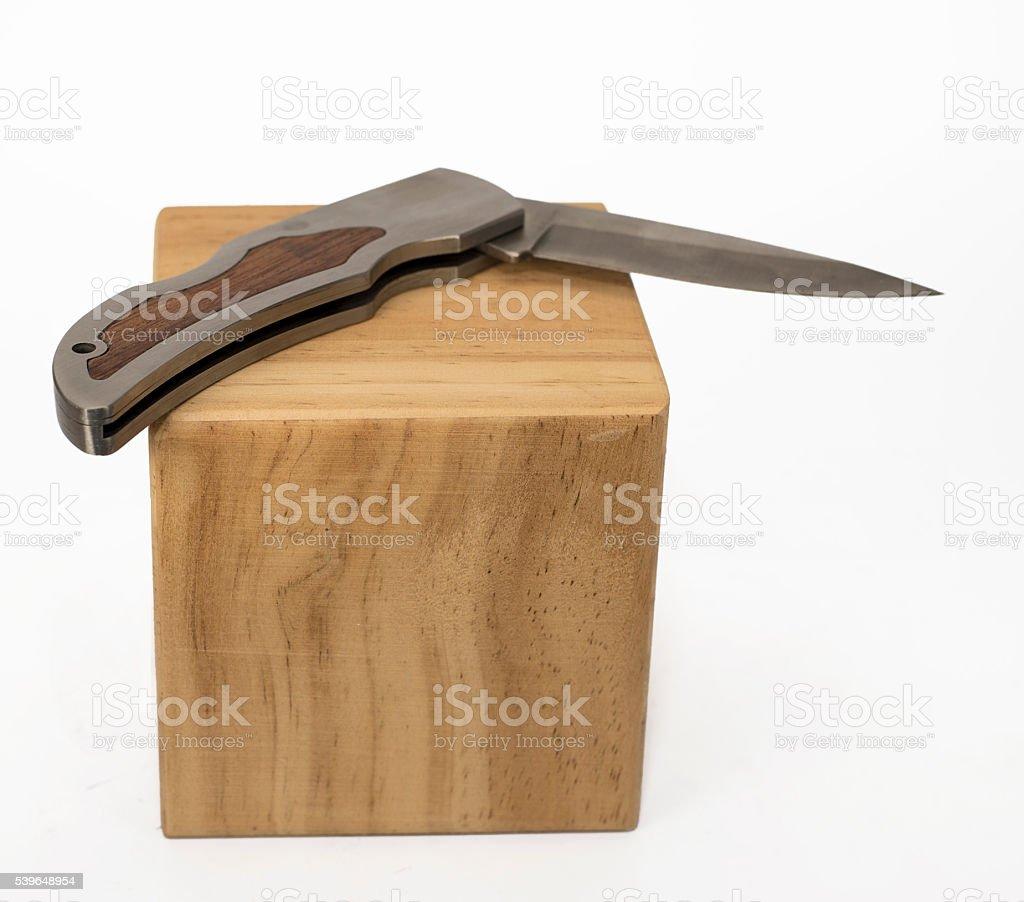 Folding knife on wood block stock photo