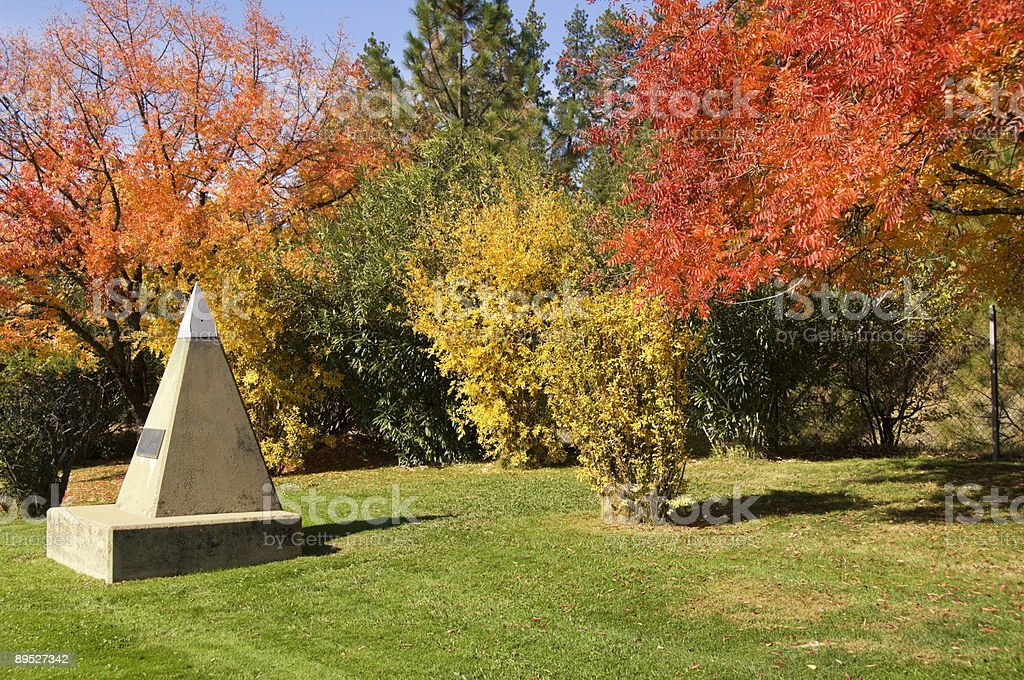 foliage in park with pyramid monument stock photo