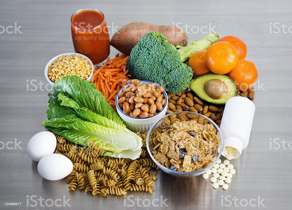 Folic Acid supplement and foods on stainless kitchen counter stock photo