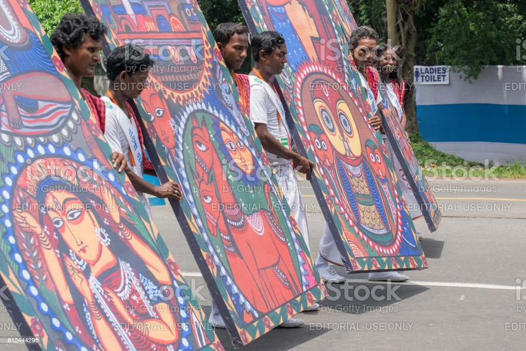 Folk dancers marching past with hoardings stock photo