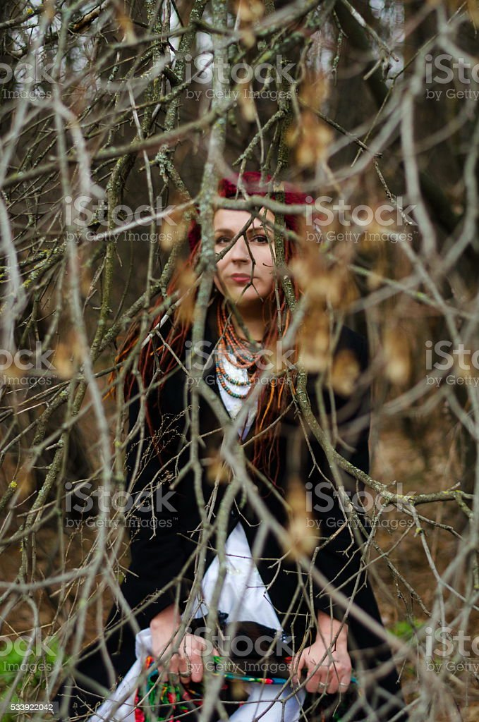 Folk-style girl in a white wedding dress in a forest stock photo