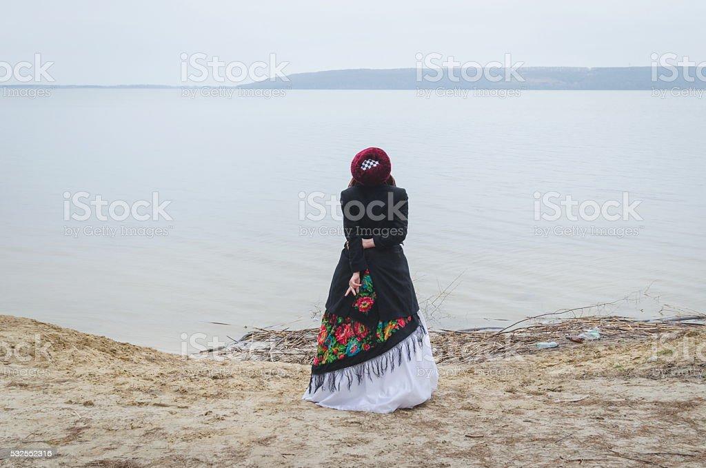 Folk-style girl in a white wedding dress near a lake stock photo