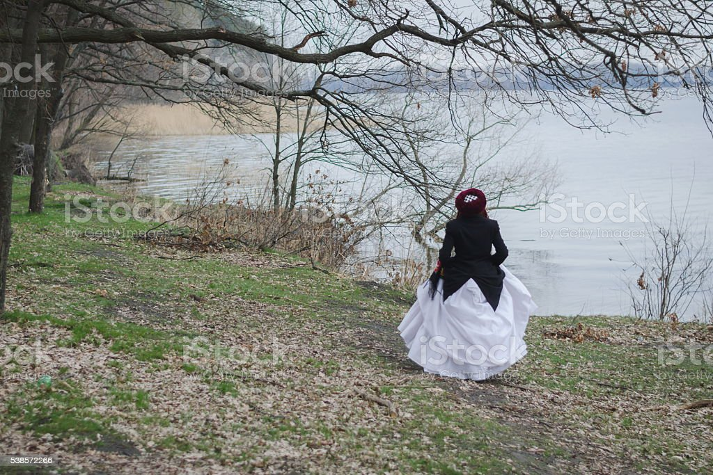 Folk-style girl in a white wedding dress near a lake stock photo