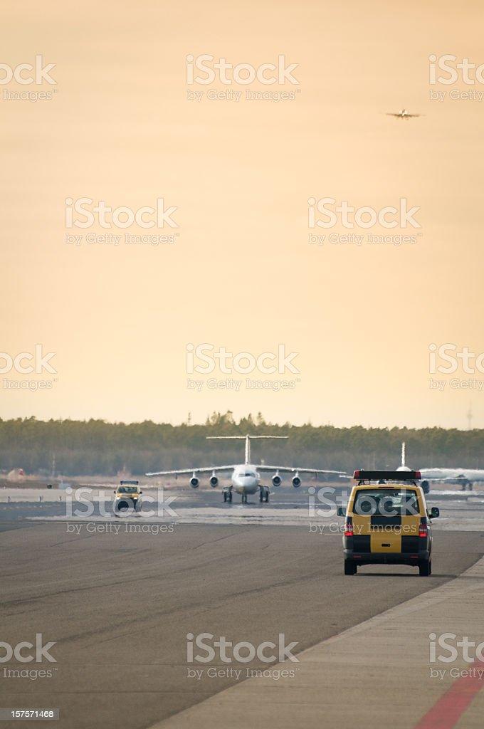 Follow me car on airport runway, airplane landing, busy tarmac stock photo