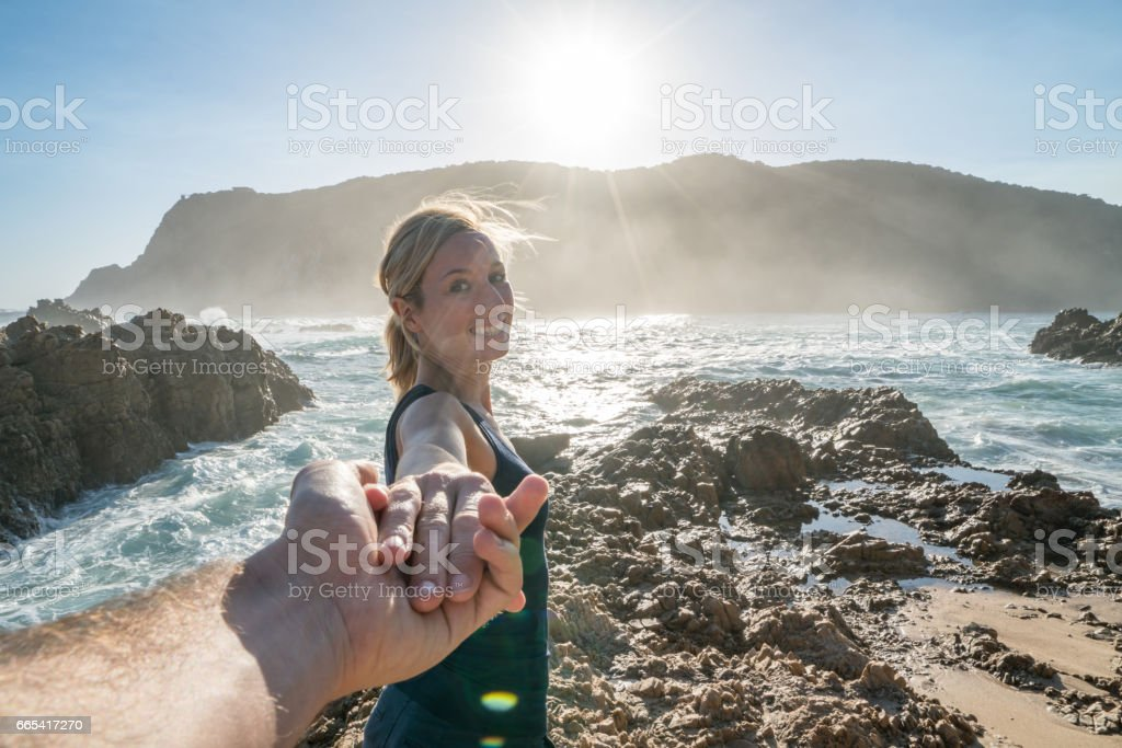 Follow me concept- Young woman leading boyfriend at the edge of the sea stock photo