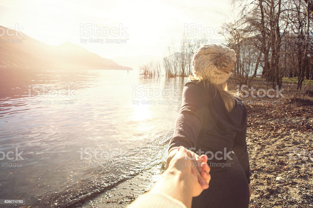 Follow me concept. Young woman walking by the lake shore holding...