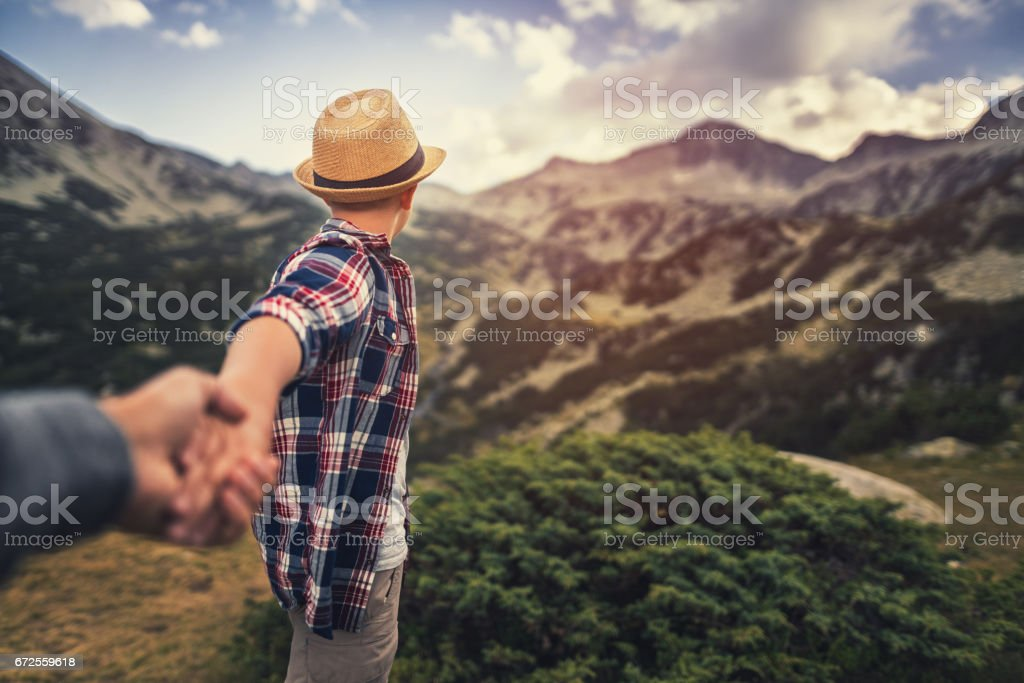 Follow me. Young boy showing the way during hiking activities stock photo