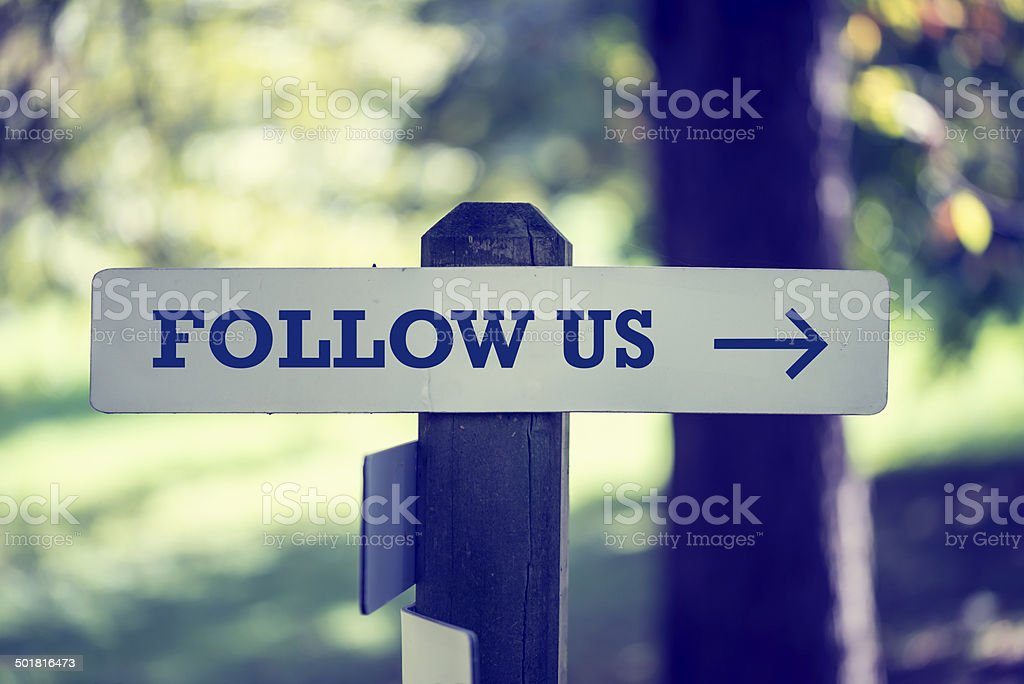 Follow Us signboard on a wooden post stock photo