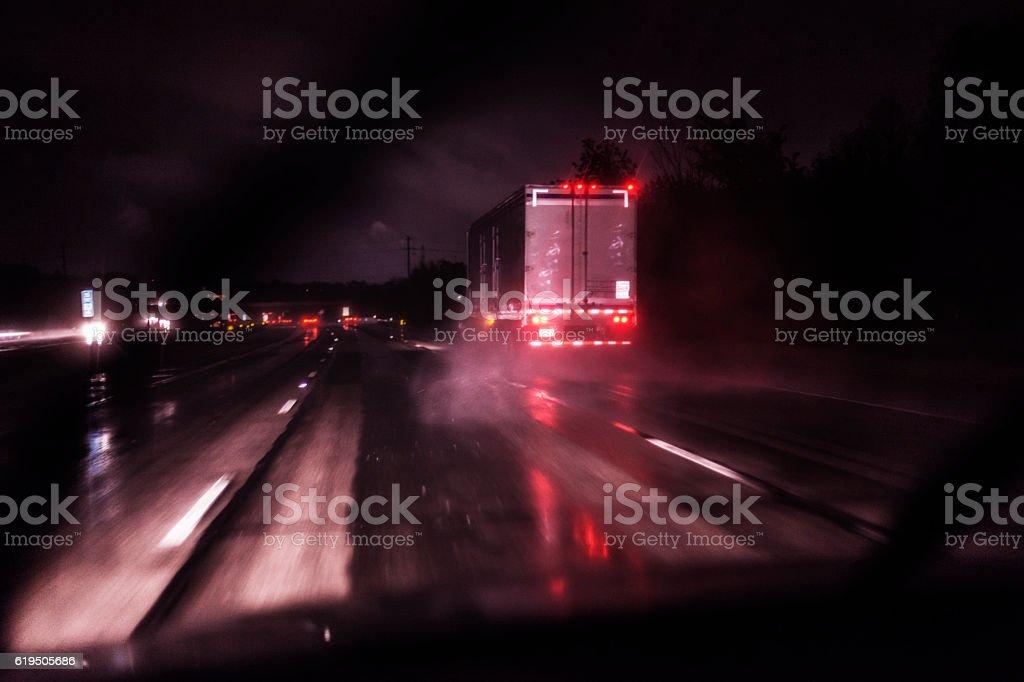 Following Rain Storm Drenched Night Expressway Speeding Semi Trailer Truck stock photo