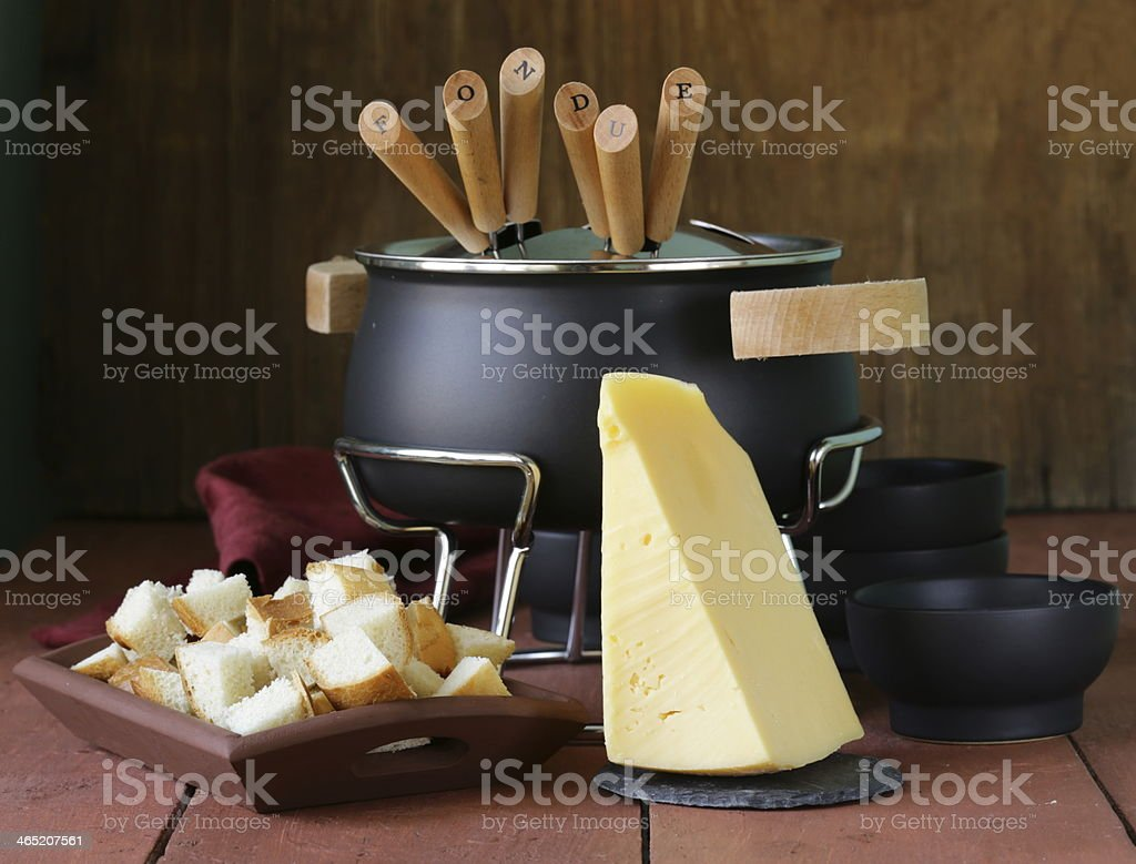 A fondue pot with a block of cheese and bread squares stock photo