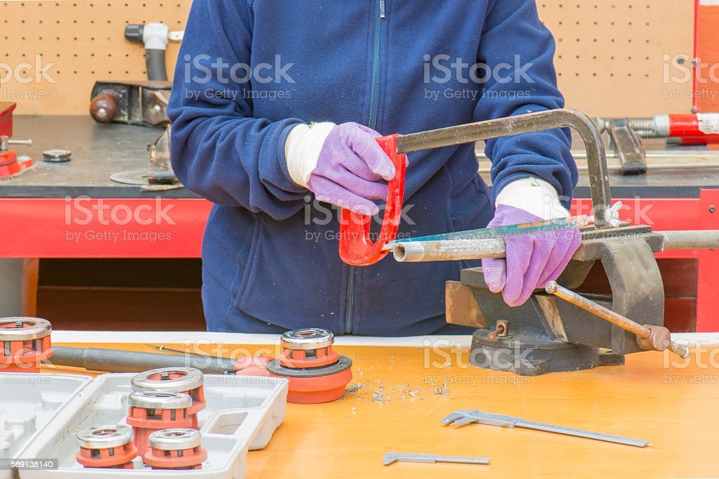fontanero cortando una tuberia photo libre de droits