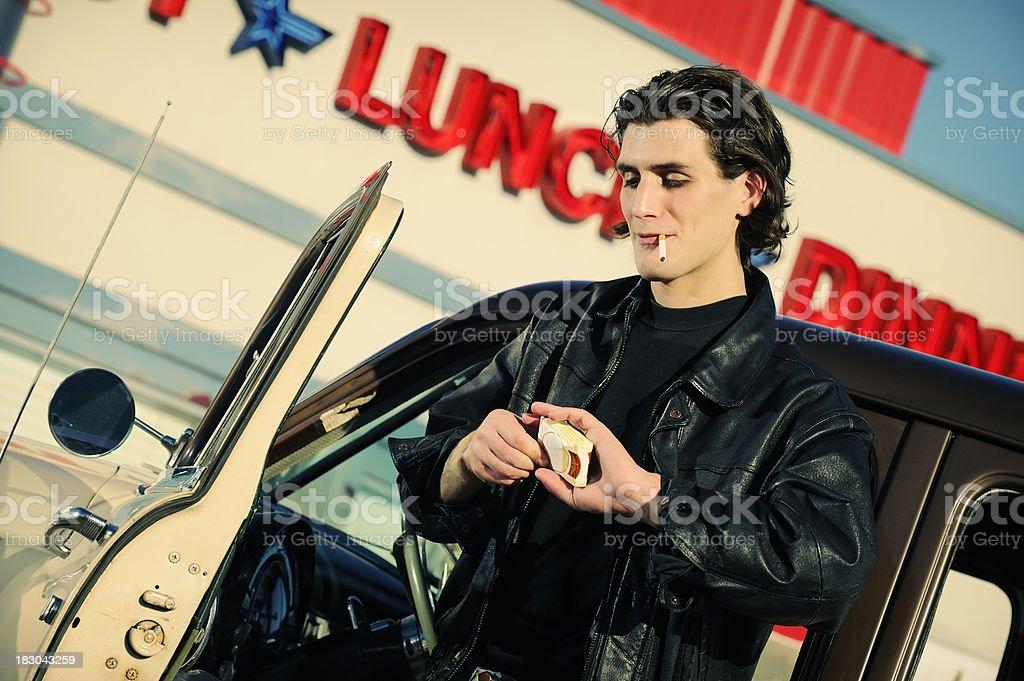 Fonzi Like Man Enjoying Cigarette Outside A Retro Diner royalty-free stock photo