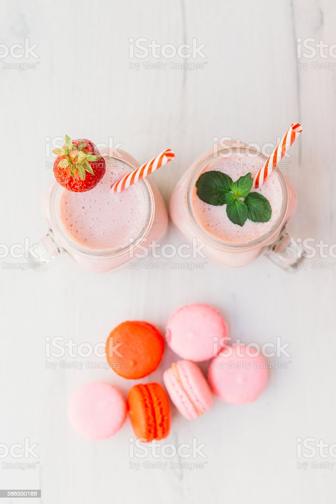 Strawberry milkshake and macaroons on wooden table