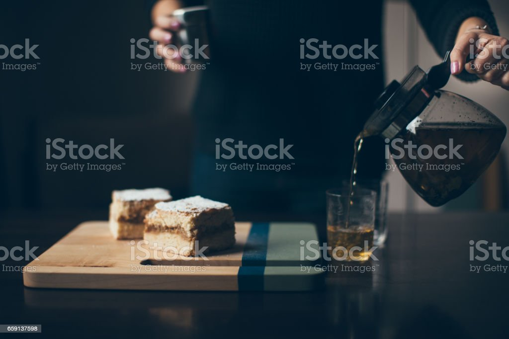 Woman hands pours tea beside wooden board with pies