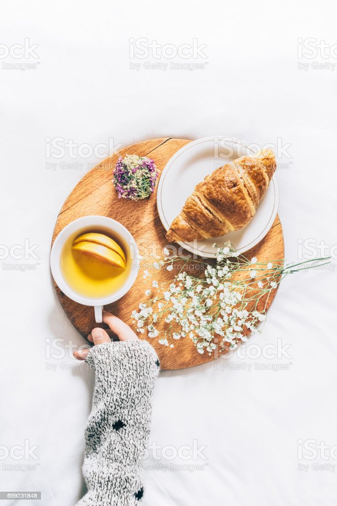 Woman hands holding cup of tea. Top view of breakfast in bed