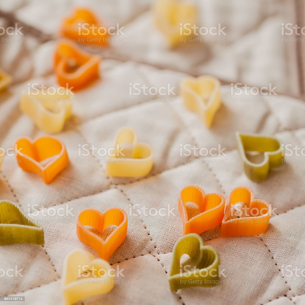 Food background. Italian tricolor pasta in the shape of hearts on the kitchen textiles. Selective focus. Close-up colorful macaroni stock photo