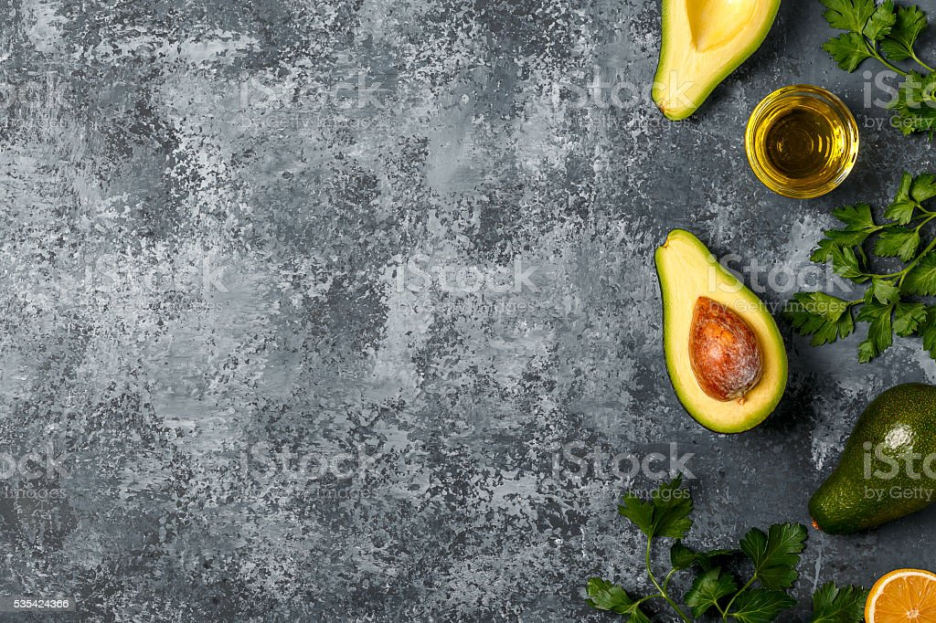 Food background with avocado, lemon, parsley and olive oil. stock photo