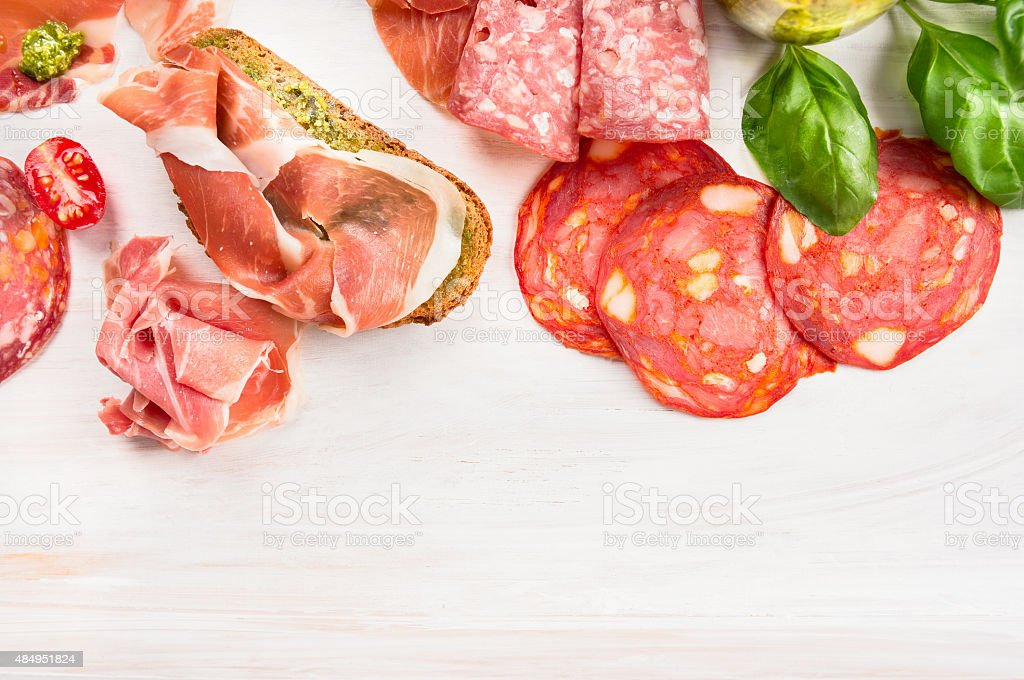 Food background with Different Italian sausage, ham and pesto sandwich stock photo