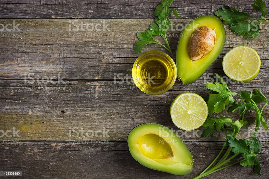 food background with fresh organic avocado, lime, parsley and ol stock photo