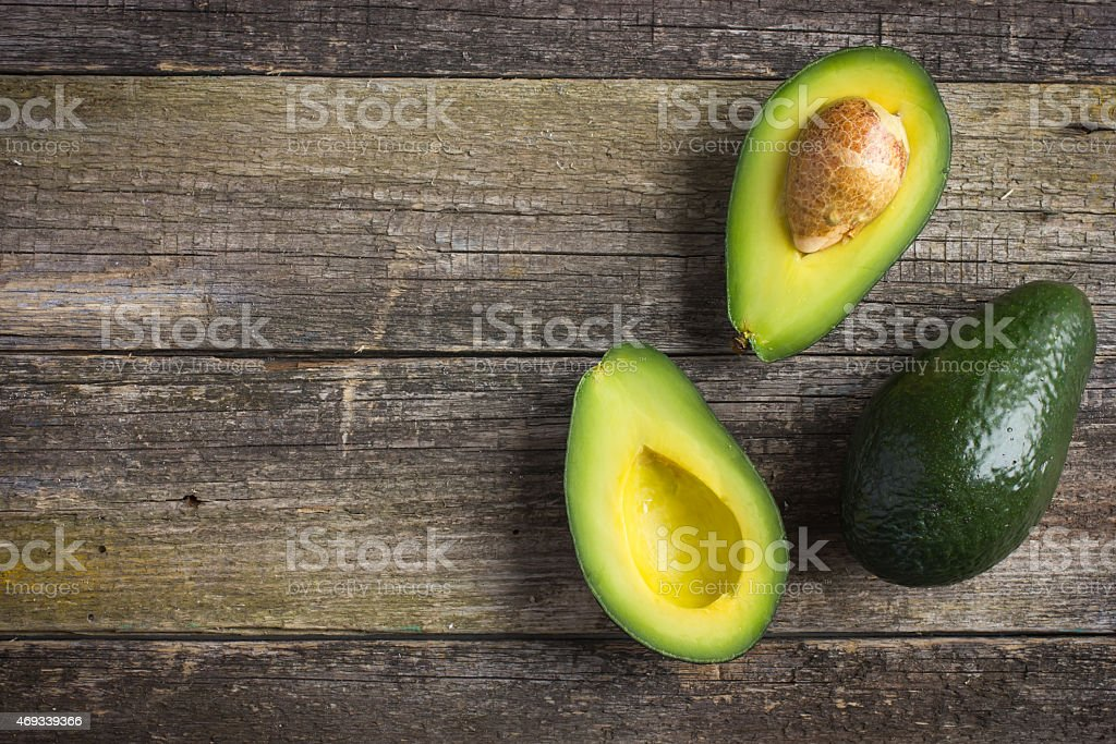 food background with fresh organic avocado on  old wooden table stock photo