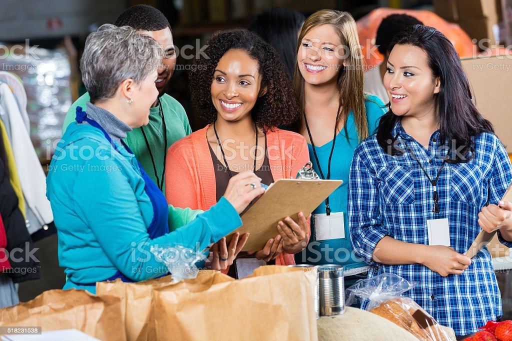 Food bank manager talks with volunteers stock photo