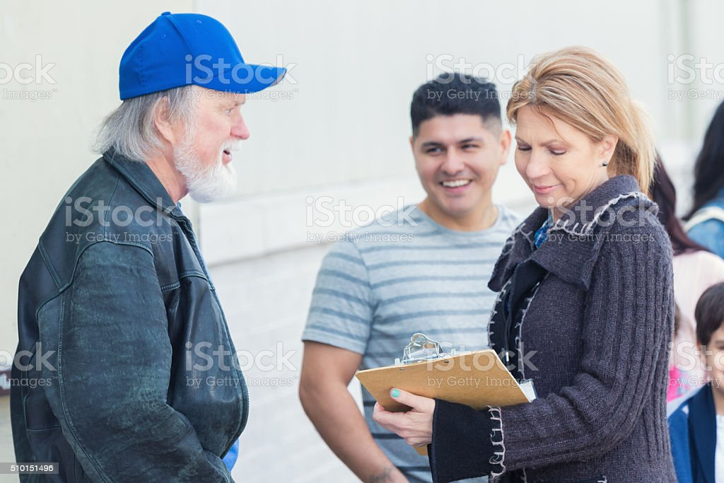 Food bank volunteer helps homeless man stock photo