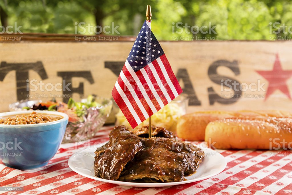 Food:  BBQ ribs, beans, potato salad and an American flag. royalty-free stock photo