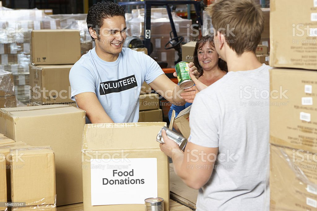 Food donations being boxed up by volunteers in a warehouse stock photo