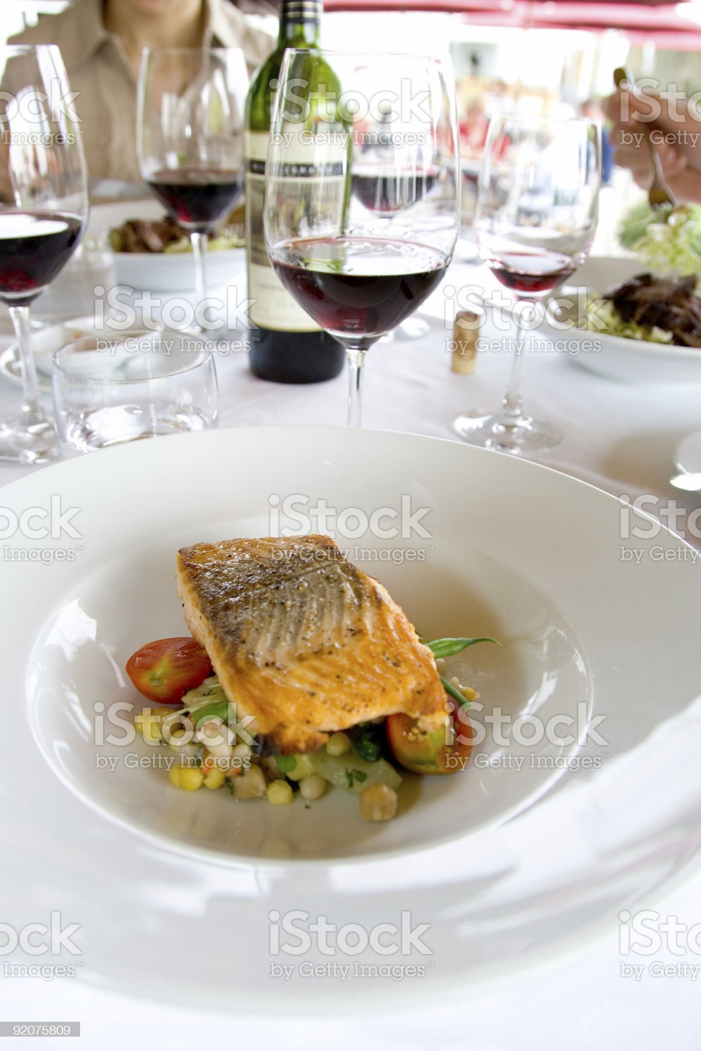 Food - Eating Grilled Salmon on Mixed Greens with Friends royalty-free stock photo
