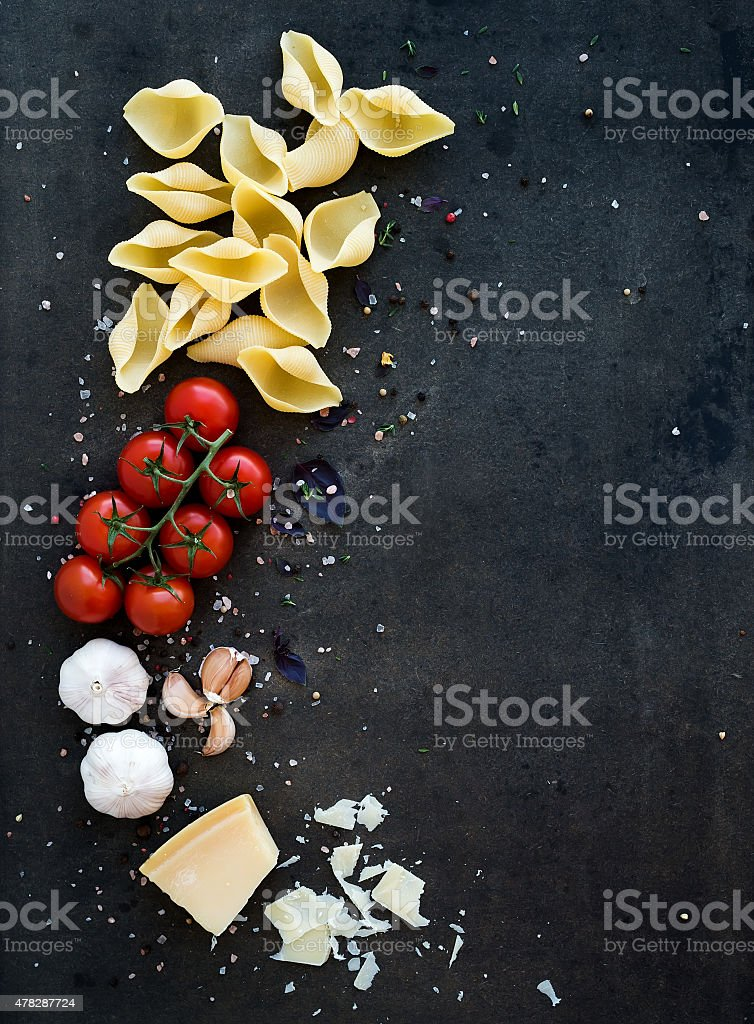Food frame. Pasta ingredients. Cherry-tomatoes, pasta, garlic, basil, parmesan stock photo