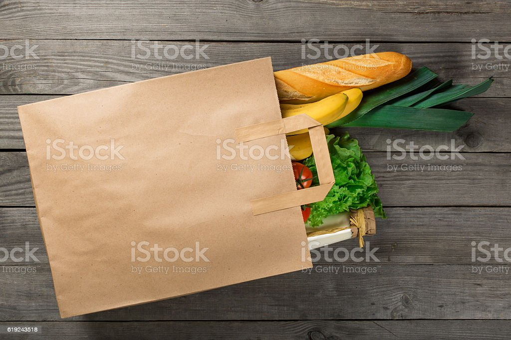 Food in paper bag on wooden background stock photo