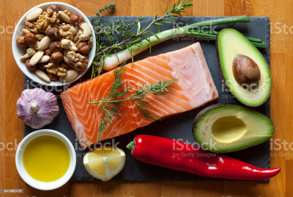 Table top still life of foods high in healthy fats such as Salmon,...