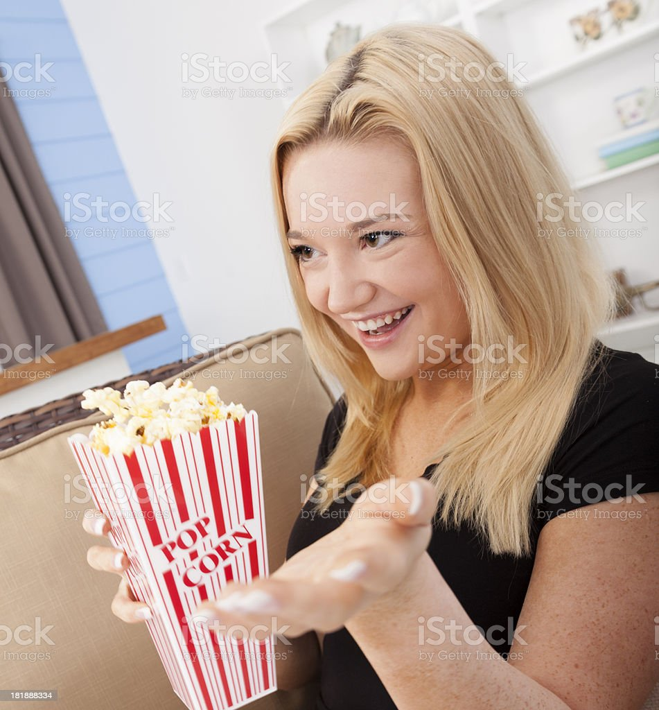 Food:  Lovely blonde young adult eating popcorn and watching TV. royalty-free stock photo