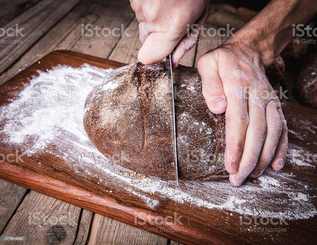 food. man's hands cut bread, homemade stock photo