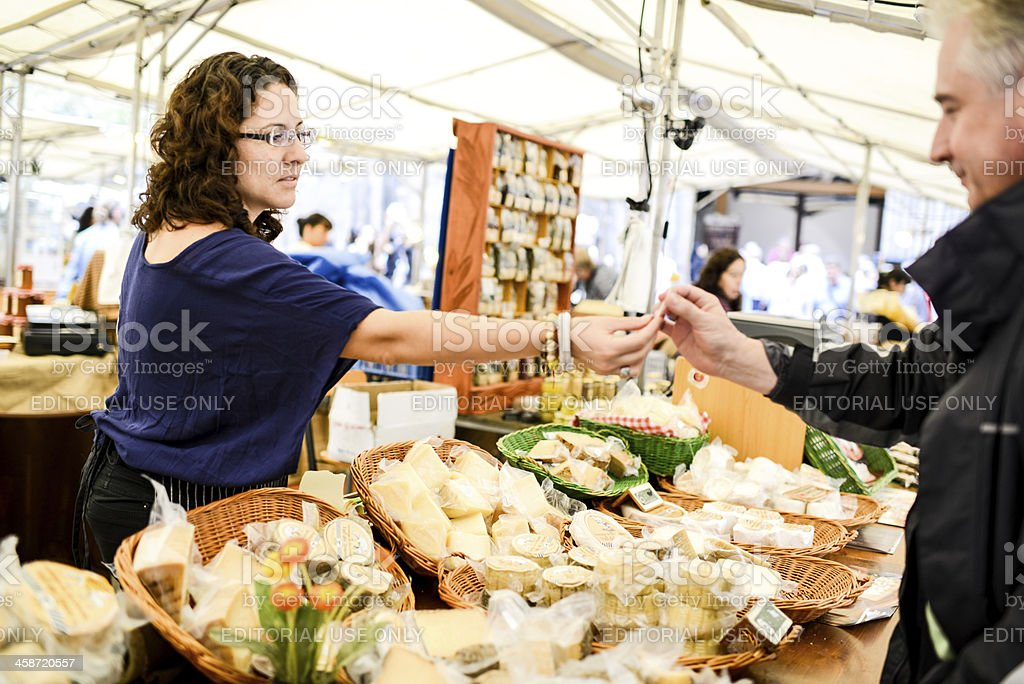 Food Market vendor giving cheese to a customer for degustation stock photo