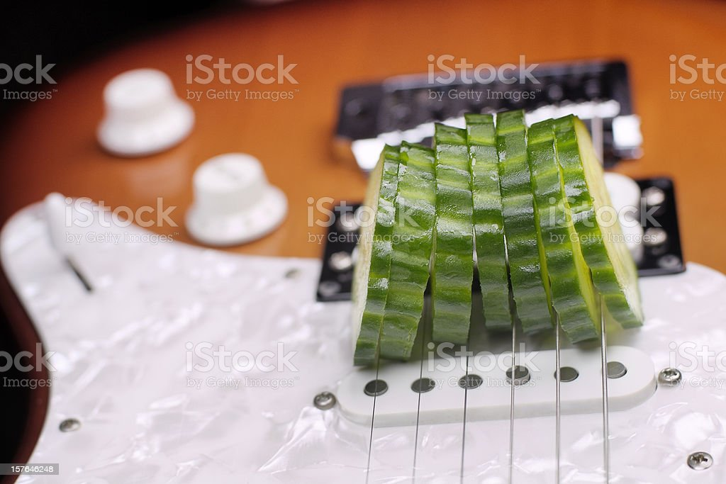 Food music - electric guitar used to slice a cucumber stock photo