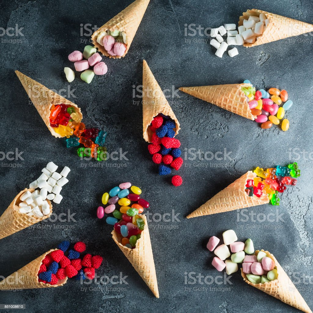 Food pattern of colorful bright assorted candy in waffle cones on dark background. Flat lay, top view stock photo
