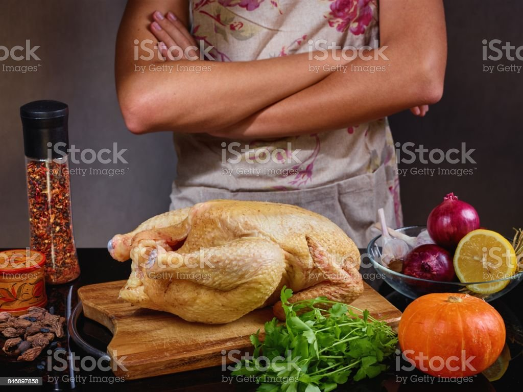 food photo  of unrecognizable man cooking chicken in the kitchencook in apron on grey background stock photo
