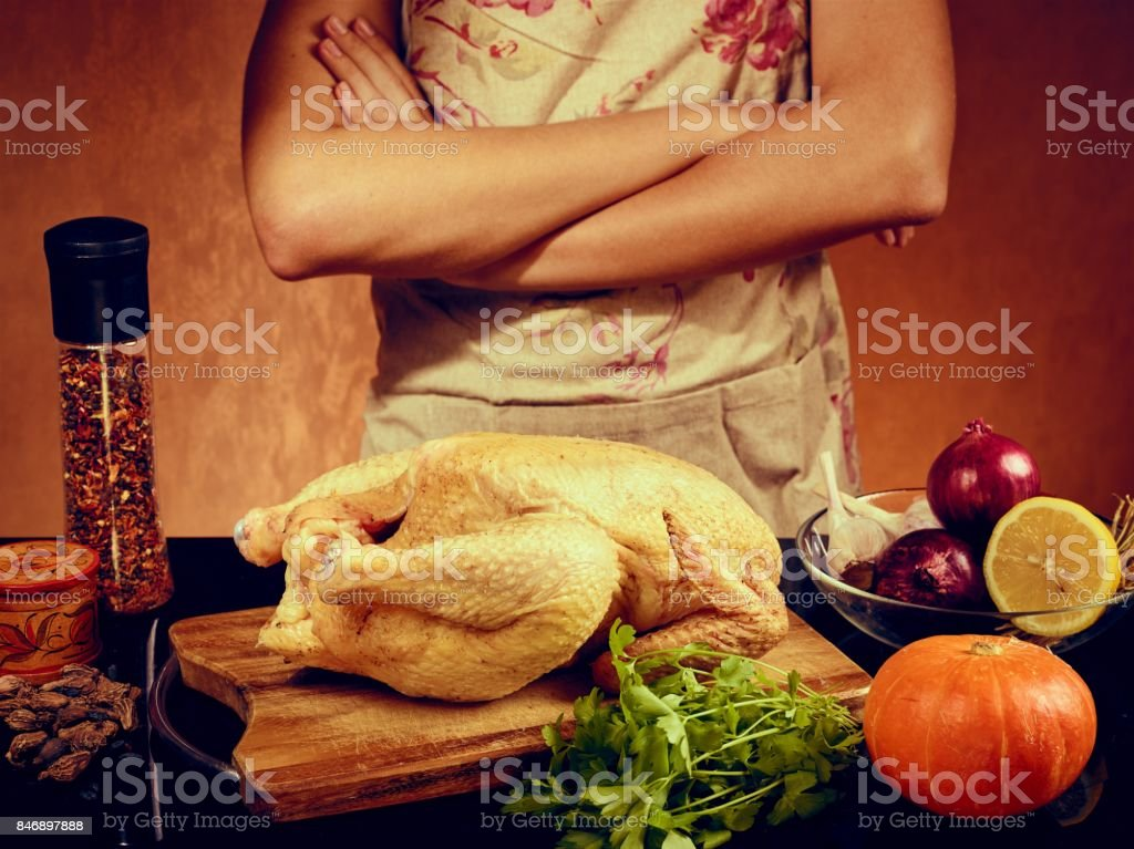food photo  of unrecognizable man cooking chicken in the kitchencook in apron on orange background stock photo