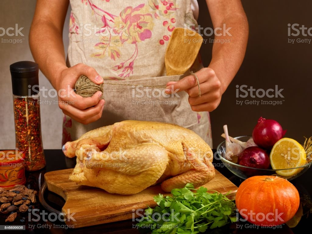 food photo  of unrecognizable man cooking chicken in the kitchencook in apron with rope stock photo