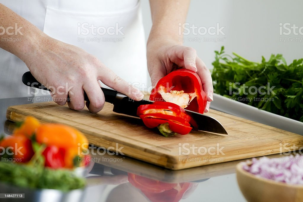Food Preparation - Cutting a Red Bell Pepper royalty-free stock photo