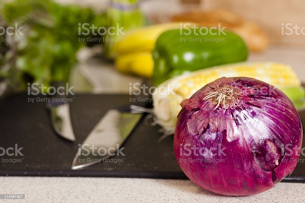 Food:  Red onion and other vegetables  cutting board with knife royalty-free stock photo