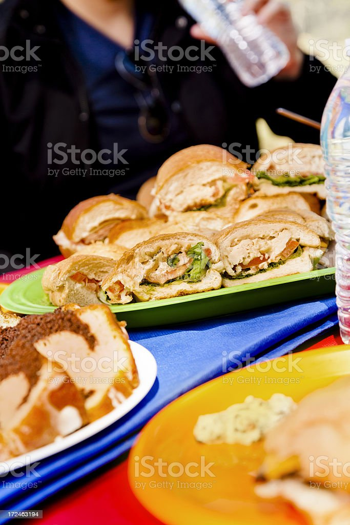 Food:  Sandwiches and cake outside on picnic table royalty-free stock photo
