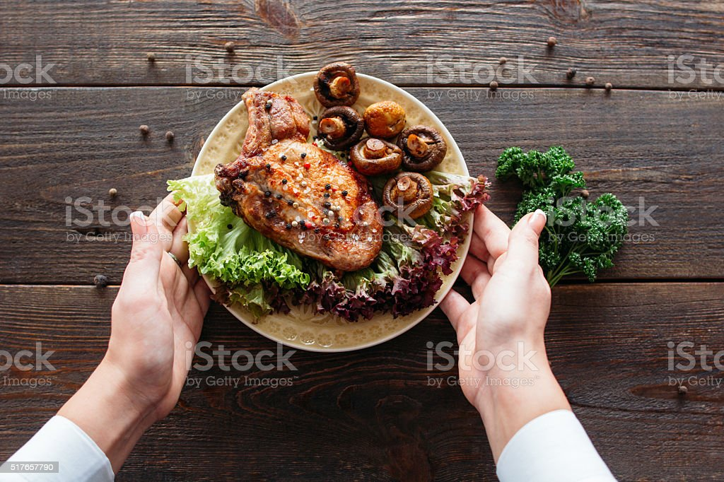 Food serving. Waiter serving a chicken dish. stock photo