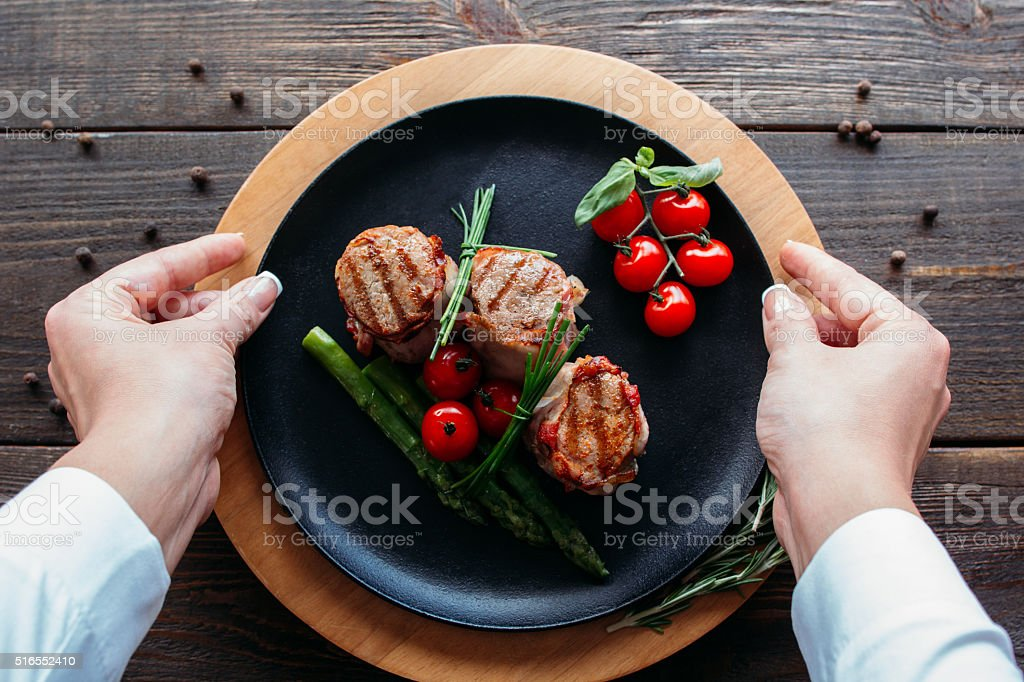 Food  serving. Waiter serving a pork dish. stock photo