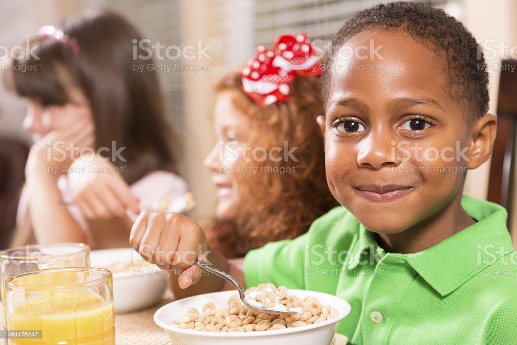 Food:  Three multi-ethnic children enjoying breakfast together. stock photo