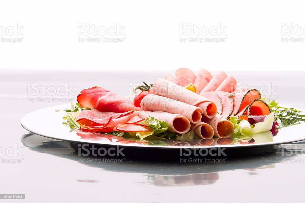 Food tray with delicious salami, pieces of sliced ham, sausage stock photo