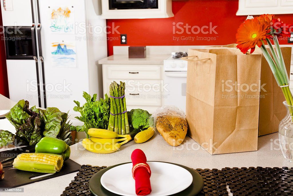 Food: Two bags of groceries and place setting at kitchen royalty-free stock photo